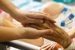 zwei junge Hände halten eine alte Hand