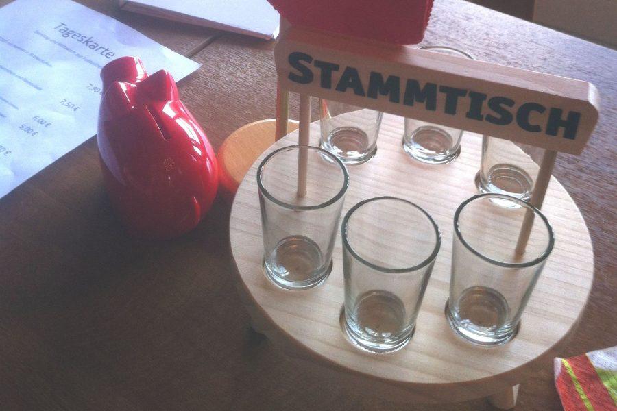 Stammtisch mit sechs kleinen Gläsern auf einem Holttablett neben einem roten Sparschwein