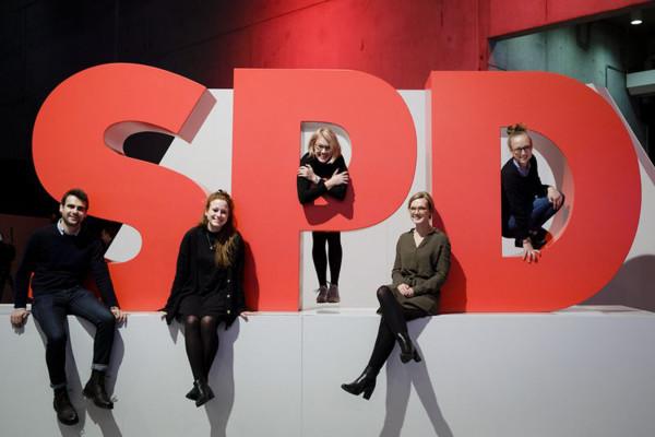 Fünf junge Menschen sitzen vor und auf drei überdimensionalen Buchstaben S, P und D
