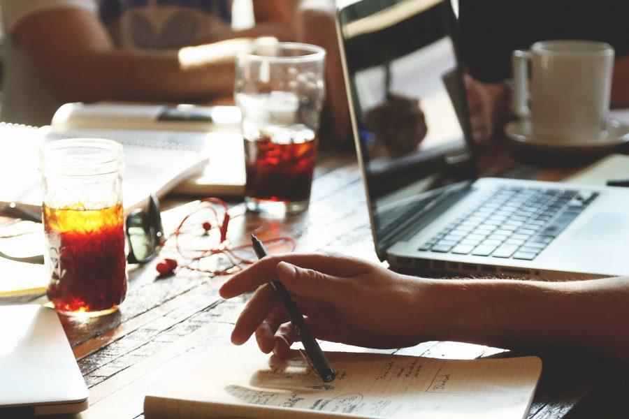 Laptop, Notizblöcke, Getränke, Hände auf einem Tisch signalisieren gemeinsames Arbeiten