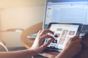 Hände tippen auf Tablet, Laptop im Hintergrund