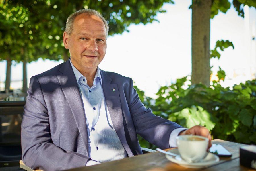 Mathias Stein sitzt in einem Café draußen mit einer Tasse Kaffee vor sich auf dem Holztisch