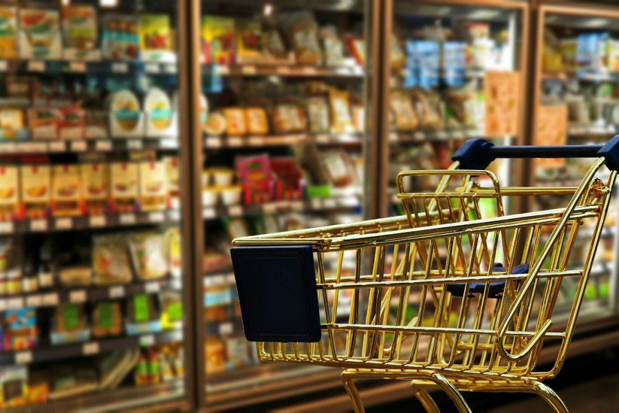 Einkaufswagen vor Kühlregal im Supermarkt