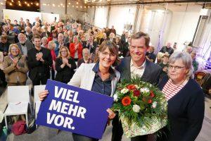 """Gesine Stück (mit einem Schild """"viel mehr vor""""), Ulf Kämpfer (mit Blumenstrauß) und Gesa Langfeldt auf der Bühne. Hinter ihnen stehen die Gäste und klatachen."""