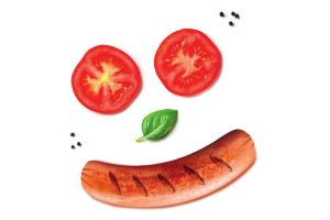 Gesicht aus Tomaten, Basilikum und Würstchen Grillfest