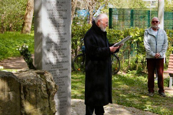 Dieter Heß steht vor dem Gedenkstein und liest etwas vor.