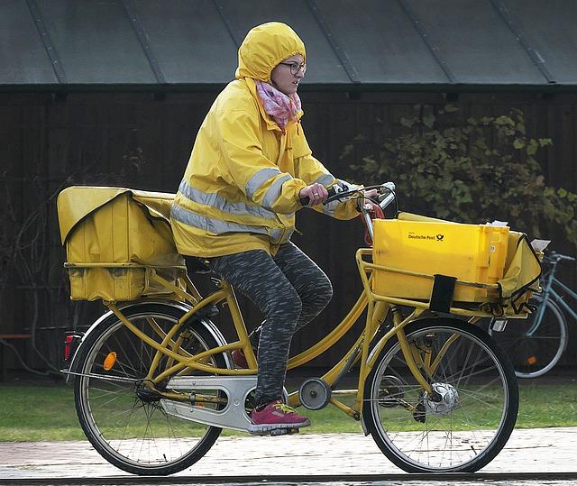 Postzustellerin auf gelben Fahrrad