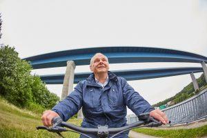 Mathias Stein auf dem Fahrrad, aufgenommen aus der Froschperspektive mit Brücke im Hintergrund.