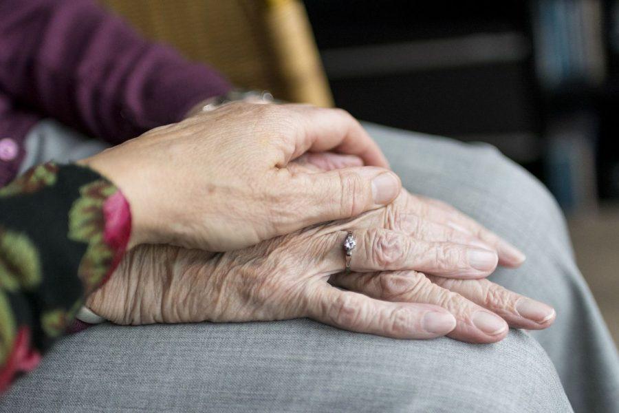 Eine Hand liegt auf der Hand einer älteren Person