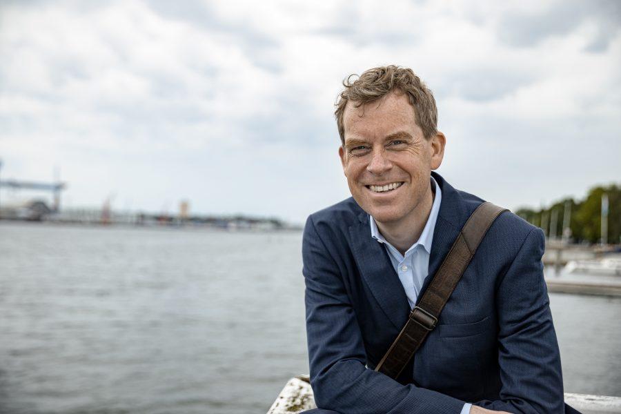 Ulf Kämpfer lächelt mit der Förde im Hintergrund