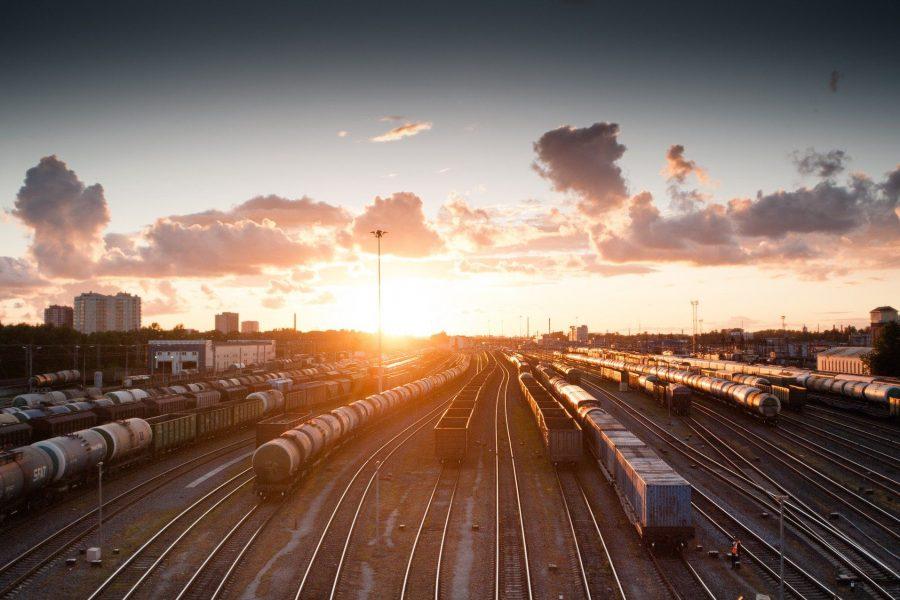 Gleise mit Zügen vor einem Sonnenuntergang