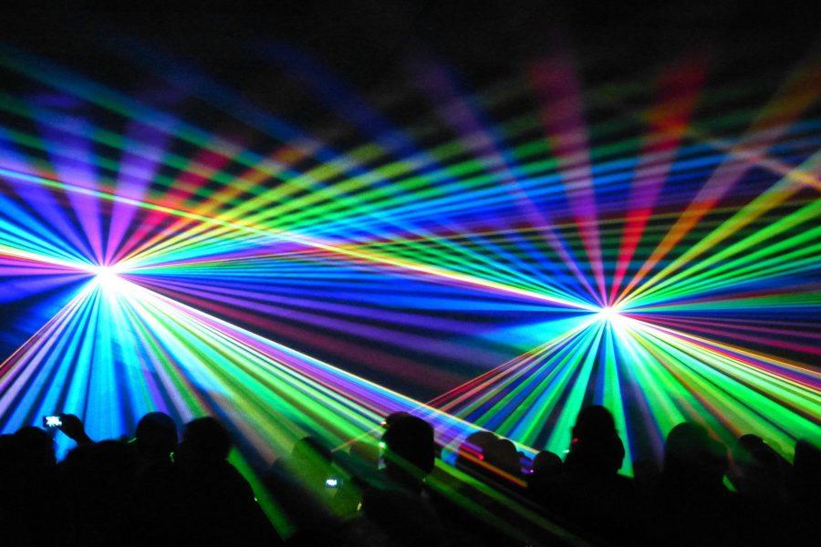 Eine Laser-Show/ein Lichterspiel bei Nacht, die sich eine unbestimmte Anzahl von Personen (nur als Silhouette sichtbar) ansehen