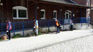 4 Männer mit orangen Warnwesten sammeln Müll an einer Rampe vor einem Haus mit Holzfassade