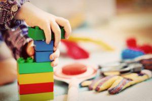 Kind baut mit Duplosteinen einen Turm. Spielzeug im Hintergrund.