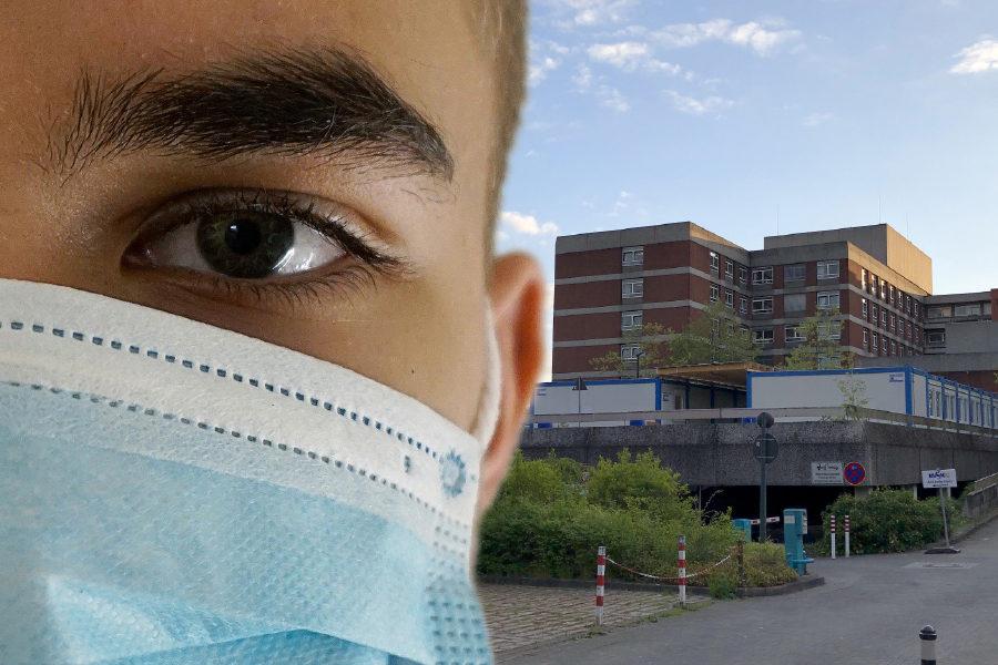 Das Bild zeigt einen Mann mit Mundschutz im Vordergrund und im Hintergrund das Städtische Krankenhaus Kiel.