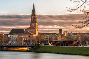 Dieses Foto zeigt den kleinen Kiel im Vordergrund und den Kieler Rathausturm im Hintergrund bei Abenddämmerung sowie einen fahrenden Bus leicht unscharf in Bewegung...