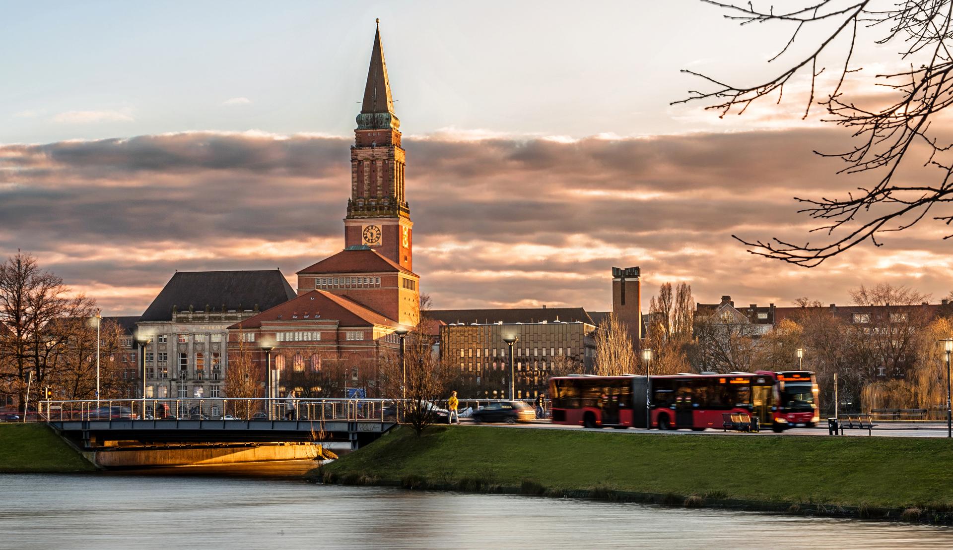Kieler Rathaus in der Abenddämmerung. Bus, Autos und Fußgänger auf der Brücke über den Kleinen Kiel