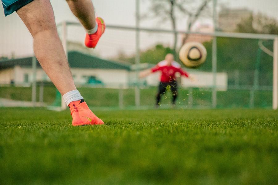 Beine eines Mannes, der einen Fußball gerade ins Tor schießt. Im Hintergrund unscharf der Torwart im Tor auf einem Raseplatz.