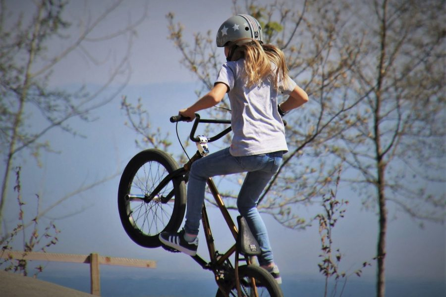 Mädchen mti Helm auf einem BMX-Rad in der Luft.