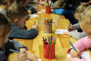 Mehrere Kinder sitzen an einem langen Tisch und malen mit Bundstiften auf Papier