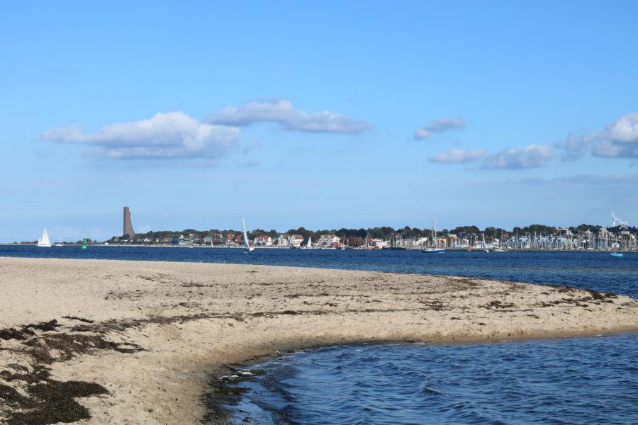 Das Foto zeigt den Falckensteiner Strand mit Blick auf die Kieler Förde. Im Hintergrund ist Laboe mit seinem Denkmal zu erkennen.