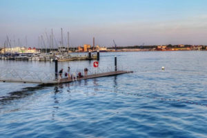 Badesteg an der Kiellinie in den frühen sommerlichen Abendstunden. Im Hintergrund Segelboote, StenaLine und Ostufer
