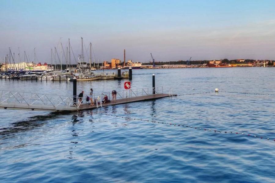 Das Foto zeigt einen Badesteg an der Kiellinie an den frühen sommerlichen Abendstunden. Im Hintergrund kann man die StenaLine und das Ostufer erkennen.