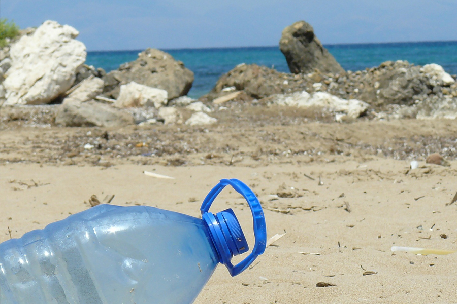 blaue benutzte Plastiktrinkflasche liegt am Strand im Hintergrund Felsen und Meer