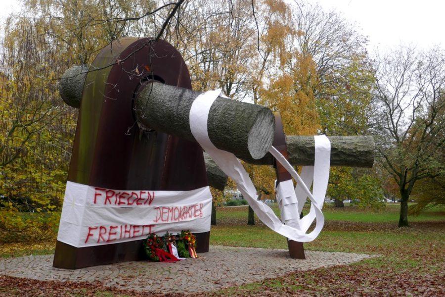 Breuste-Denkmal mit Papierbahnen umwickelt auf denen steht: Frieden, Demokratie, Freiheit. Davor liegen drei Kränze.