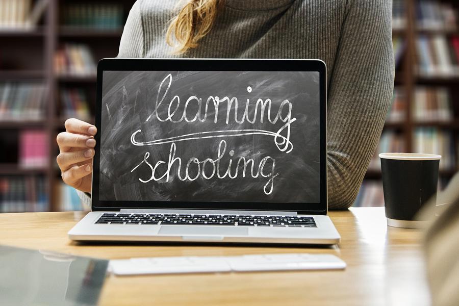 """Display eines Laptop auf dem mit Kreide geschrieben steht """"learning schooling"""". Im Hintergrund Frau, die den Laptop hält und ein Bücherregal"""