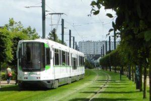 Tram auf Rasenbett mit Hochhäusern im Hintergrund