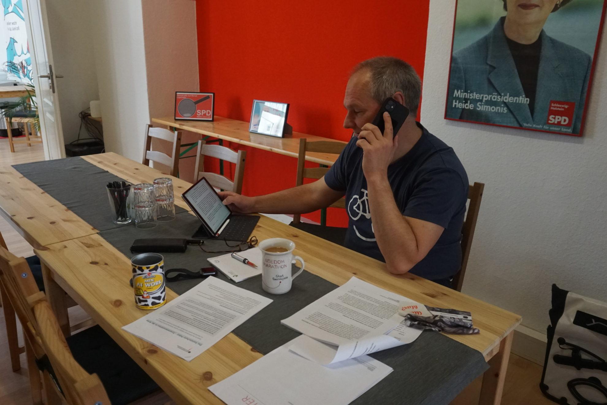 Mathias Stein telefoniert im Bürgerbüro, guckt gleichzeitig auf sein Tablet. Hinter ihm ist ein Plakat von Heide Simonis, neben ihm eine Tasse Kaffee und mehrere Unterlagen.